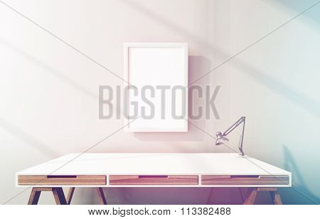 Modern drafting or drawing table with drawers and a blank picture frame on the wall above in a shaft of colorful sunlight, 3d render