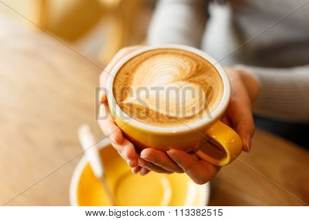 lady's hands hold cup filled with something heart-shaped