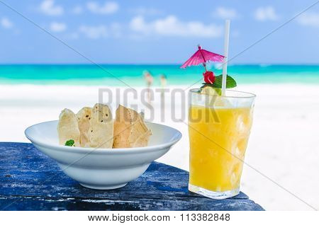 Fresh Cocktail With Orange Juice And Nachos On Table At Tropical Exotic Caribbean Beach