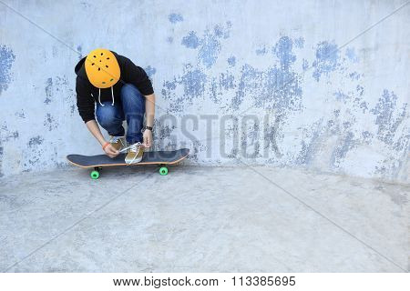 one young skateboarder tying shoelace at skatepark