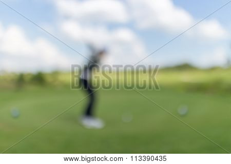 Blurred Photo Of Golf Player On Green With Beautiful Nature Scene.