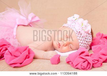 A sleeping newborn baby girl wearing a pink headband and tutu