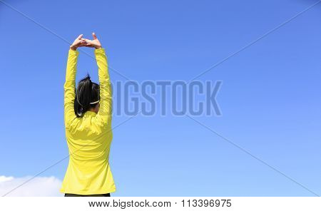young fitness woman runner stretching arms on mountain peak under blue sky