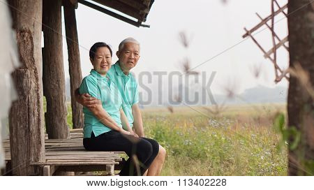 Asian Senior Couple Sitting In The Gazebo Next To Rice Field
