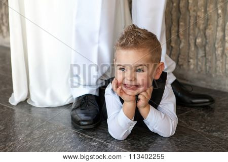The little happy boy lies on a floor at a wedding