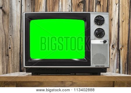 Analog television on wood wall and chroma key green screen.