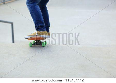 closeup of one skateboarder legs skateboarding on skatepark ramp