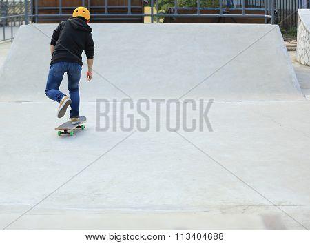 closeup of one skateboarder skateboarding on skatepark ramp