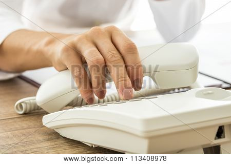 Female Hand Holding A White Landline Telephone Handset And Dialing A Phone Number
