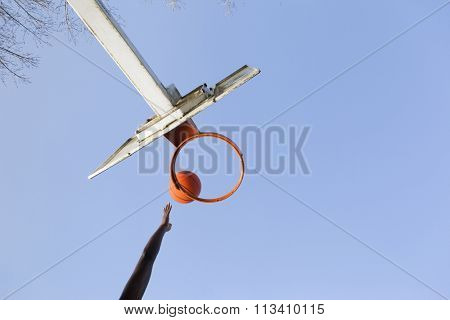 Basketball player jumping to dunk against blue sky
