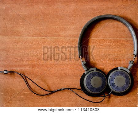 Black headphone on the old wood board