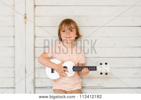 Little happy boy plays his guitar or ukulele