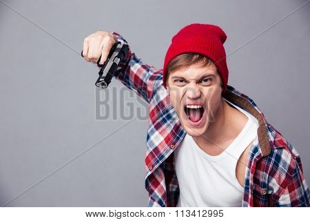 Dangerous agressive young man in checkered shirt and red hat shouting and threatening with gun over grey background
