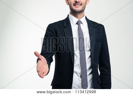 Cheerful attractive young businessman in black suit and tie giving hand for handshake over white background