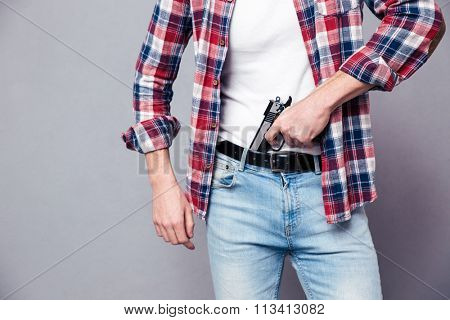 Man putting a gun in his jeans pants over gray background