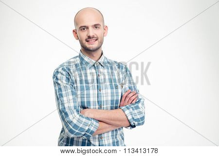 Happy handsome young man in checkered shirt standing with arms crossed over white background