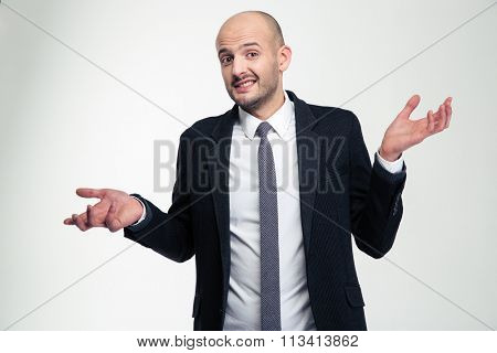 Confused embarrassed young businessman holding copyspace on both palms over white background