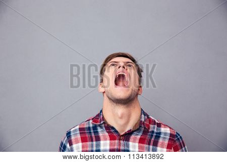 Despaired angry young man in plaid shirt looking up and screaming over grey background