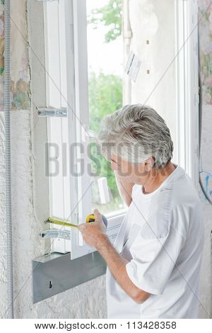 Mason measuring a window