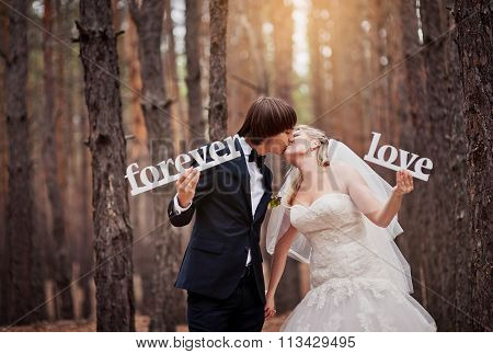 Groom Kissing The Bride At A Wedding In The Autumn Forest And Holding In Their Hands The Letters