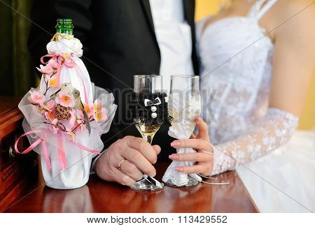 Bride And Groom Holding Beautifully Decorated Wedding Glasses With Champaign