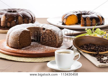 Chocolate Cake On The Table With Carrot Cake In The Background.