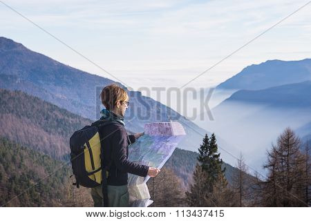 Woman Reading Trekking Map On The Alps