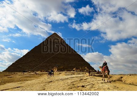 A Camel rider travels toward the Great Pyramid of Giza (Khufu) - Cairo, Egypt