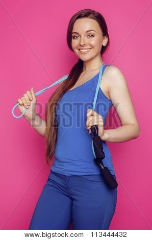 young happy slim girl with skipping rope on pink background smiling sweety cute , good shape