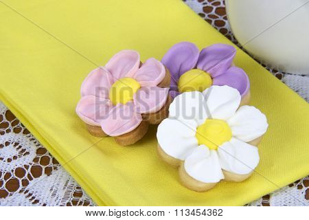 flower sugar cookies on yellow napkin lace table cloth white cup