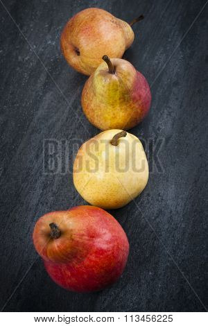 Four bright ripe bartlett pears on dark grey background from above