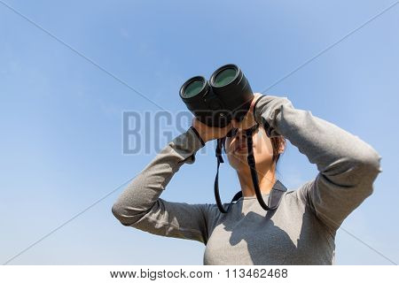 Asian Woman looking though telescope
