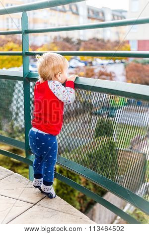 Boy Staying On Tiptoes And Watching From Balcony
