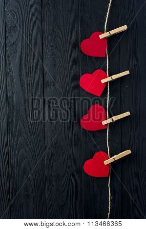 Red hearts with clothespins on dark background
