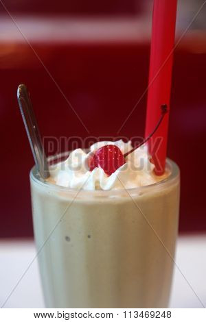 A classic Chocolate Milkshake with Whipped Cream and a Cherry, in a Glass Milkshake glass with a red straw and silver spoon.