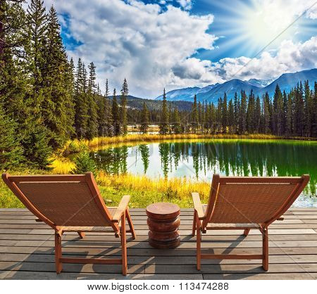 Two wooden deckchairs for tourists on the shore of shallow circular lake. Autumn day in Jasper  National Park in the Rocky Mountains of Canada