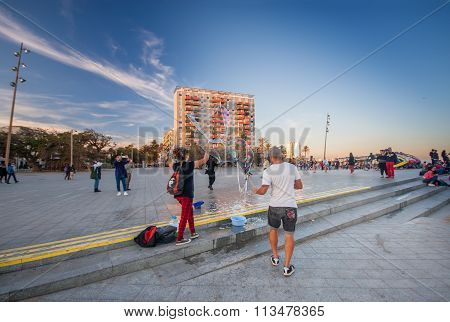 Barcelona, Spain - November 10, 2015: Unidentified Man And Woman Blow Large Soap Bubbles On Placa De