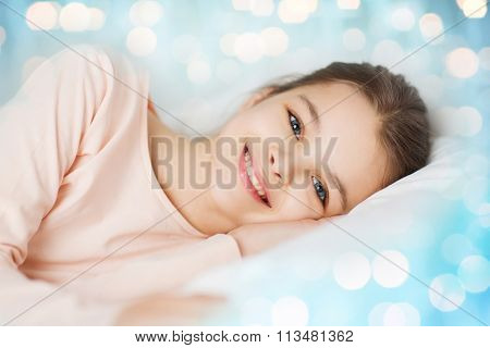 happy smiling girl lying awake in bed over lights