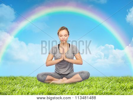 woman meditating in lotus yoga pose over rainbow