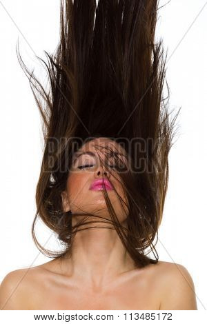 Young woman dancing with her long hair fluttering in motion, isolated on white