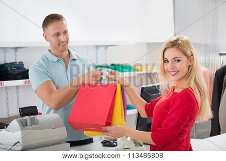 Happy Customer Taking Shopping Bags From Salesman In Store