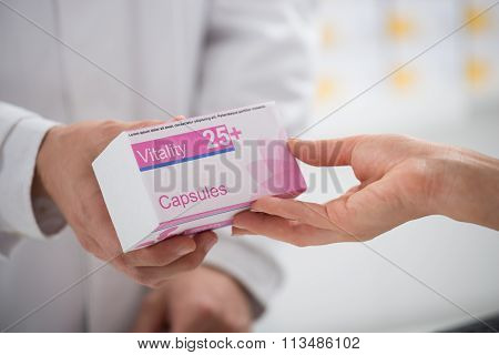 Pharmacist Giving Capsule Packet To Customer In Store