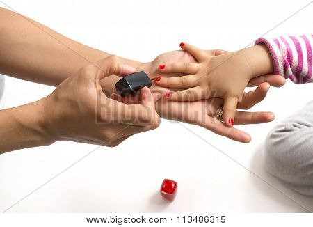 Mother Applying Nail Polish To Her Little Girl