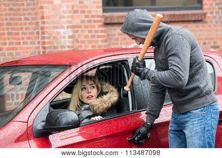 Robber Holding Baseball Bat While Looking At Woman In Car