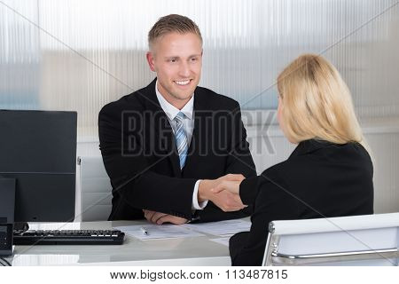 Businessman Shaking Hands With Female Candidate At Desk