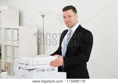 Confident Businessman Standing By Photocopy Machine