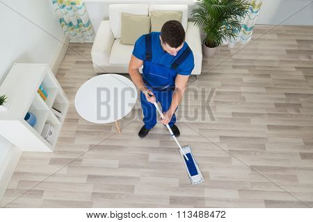 Janitor Cleaning Hardwood Floor With Mop At Home
