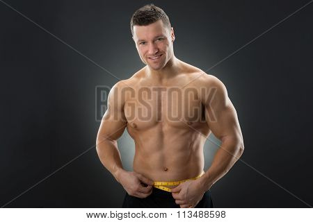 Muscular Man Measuring Waistline With Measure Tape