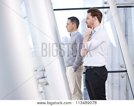 Businessmen Looking Out Of Window