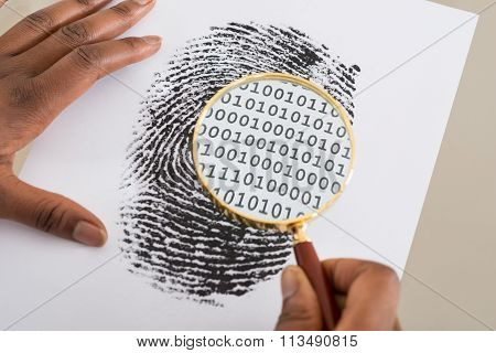 Using Magnifying Glass To Check Binary Code Within Finger Print